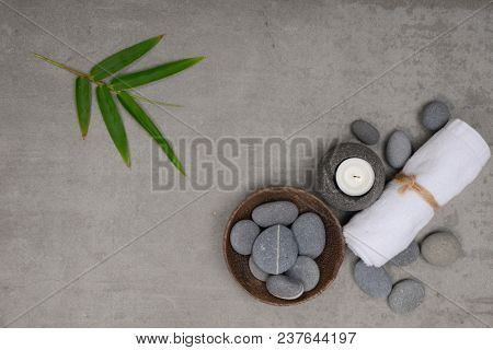 Set of many gray stones ,candle and rolled towel with bamboo leaves -gray background