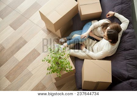 Young Millennial Couple Owners Moved Into New Home Resting On Couch On Moving Day, Happy Family With