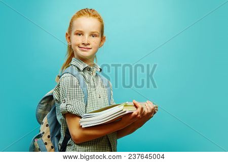 Portrait Of First-grader Schoolchild With Backpack And Notebooks In Hand On Isolated Blue Background