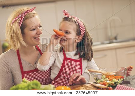 Beautiful Mother And Daughter Having Fun In The Kitchen While Cutting Vegetables For Salad; Daughter