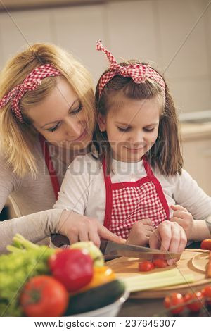 Mother And Daughter Cutting Vegetables And Making Salad. Focus On The Mother