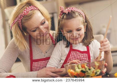 Beautiful Mother And Daughter Having Fun In The Kitchen While Making Salad; Little Girl Mixing Salad