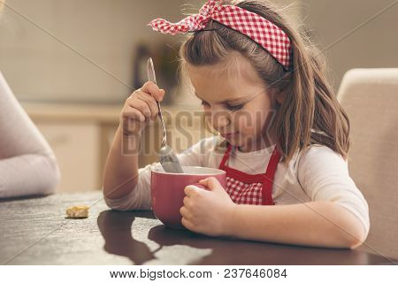 Little Girl Sitting In The Kitchen, Having Breakfast, Eating Cereal
