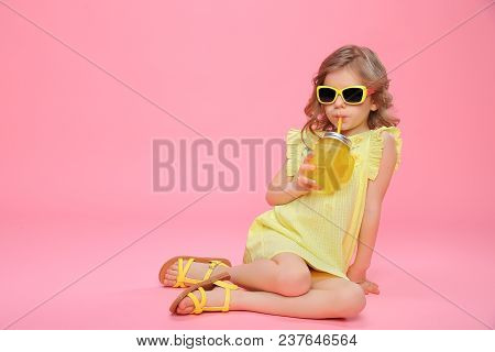 Pretty Little Girl In Dress And Sunglasses Sitting On Pink With Glass Jar Of Cocktail Chilling.