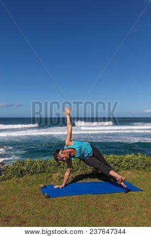 A Woman Practicing Yoga Near The Ocean On The Beautiful Island Of Maui