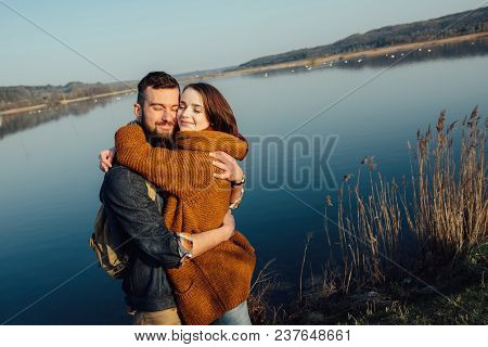Travel And Love. Happy Young Couple Walking Along The Shore Of Blue Lake In Hipster Clothes