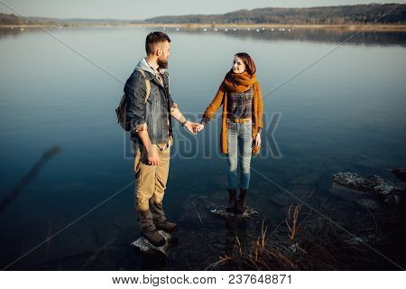 Young Loving Couple Holding Hands, Against A Blue Lake, Kissing