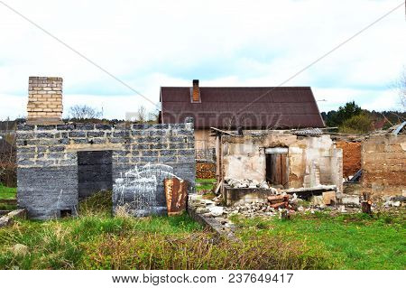 Abandoned and devastated house with fallen facade and roof and broken walls and unfinished abandoned house with bricks chimney in grass with new roof of suburban house in background. Concept of polluted and uncovered environment. poster