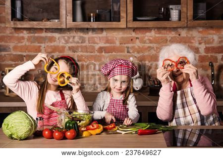Granny with two grandchildren holding sliced pepper in front of their eyes sitting at home kitchen