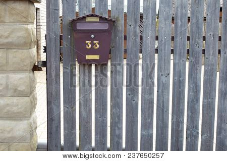 Brown Metal Mailbox On Grey  Natural Aged Wooden Fence.