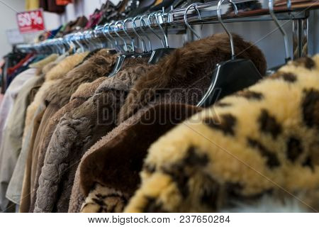 Rail of secondhand fur coats for sale in a thrift store or charity shop with a fifty per cent discount sign