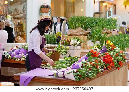 Moscow, Russia - March 8, 2017: Flower Salesman Prepares Bouquets Of Tulips For Sale In The Shopping