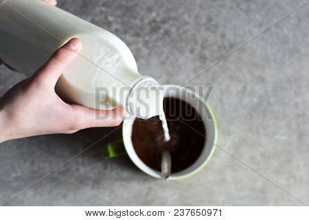 Teenage Girl Hands Pour Milk From Plastic Bottle In Big Green Mug With Cacao Drink On Grey Grunge Bl