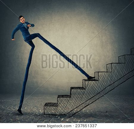 Businessman With Long Legs Stepping On A Staircase, Trying To Leap More Stairsteps Once. Accelerate