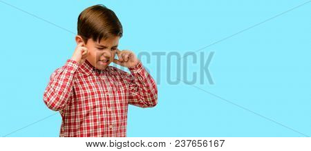 Handsome toddler child with green eyes covering ears ignoring annoying loud noise, plugs ears to avoid hearing sound. Noisy music is a problem. over blue background