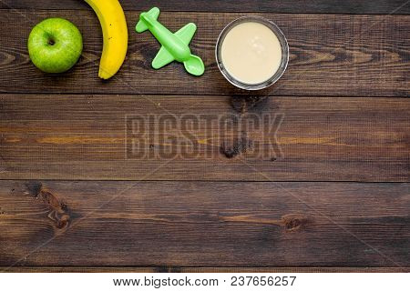 Fruit Puree For Baby. Jar With Food, Apple, Banana, Toys On Dark Wooden Background Top View.