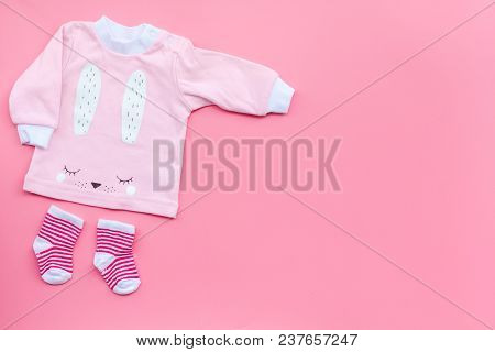 Newborn Baby's Background. Clothes For Small Girl With Booties On Pink Background Top View Copy Spac