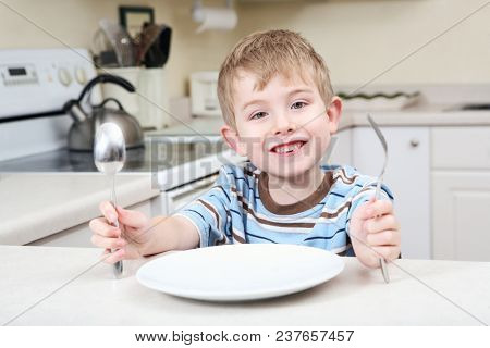 Young boy sitting in the kitchen waiting for his food