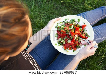 Young Girl Eating Fresh Salad On Grass. Top View.