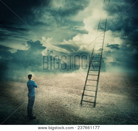 Surreal View Of A Businessman Thoughtful Looking At A Huge Ladder Going Up In The Sky Reaching The C