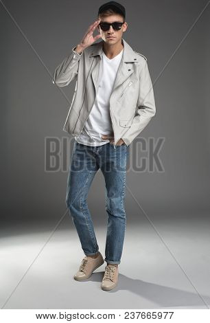 Full Length Portrait Of Serious Guy Standing In Trendy Garment And Cap. He Is Wearing Sunglasses On