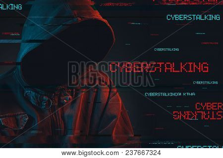 Cyberstalking Concept With Faceless Hooded Male Person, Low Key Red And Blue Lit Image And Digital G