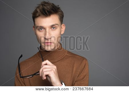 Portrait Of Young Guy Holding Glasses In Hand And Looking At Camera With Seriousness. Copy Space In