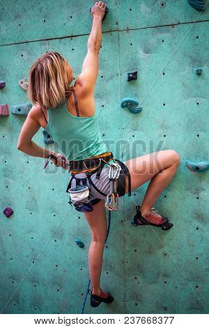 The Climber Trains On An Artificial Relief. A Woman Climbs A Climbing Route On A Street Climbing Wal