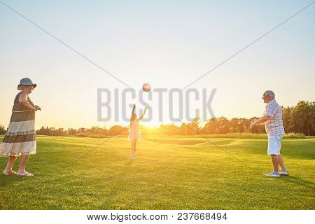 Girl With Grandparents Playing Ball. People, Green Lawn And Sky. Family As A Team.