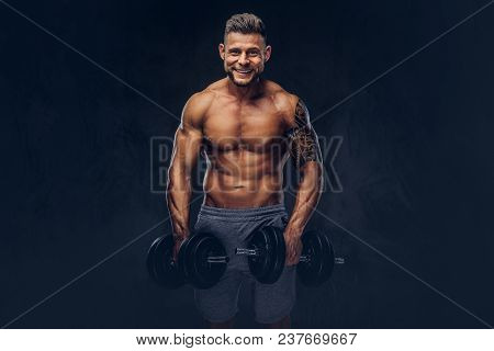 Smiling Stylish Bodybuilder With A Tattoo On His Arm, Doing The Exercises With Dumbbells. Isolated O