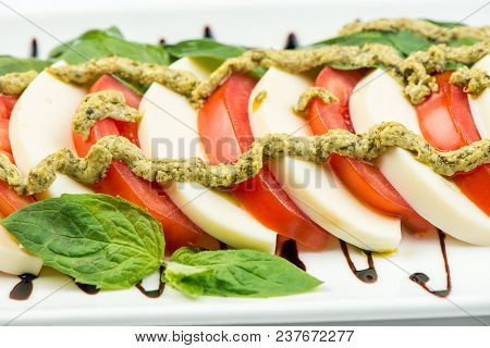 Tomatoes Coarsely Chopped With Cheese, On A Square Plate On A White Background