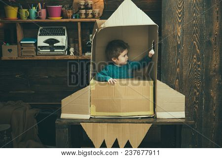 Kid Sit In Cardboard Hand Made Rocket. Childhood Concept. Boy Play At Home With Rocket, Little Cosmo