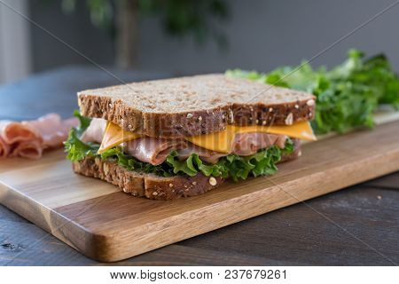 Fresh Ham And Cheese Sandwich On Whole Wheat Bread On Cutting Board