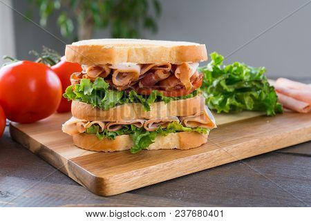 Fresh Triple Decker Turkey Club Deli Sandwich On Cutting Board