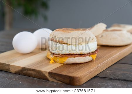 Canadian Bacon, Egg And Cheese Breakfast Sandwich With English Muffin On Cutting Board