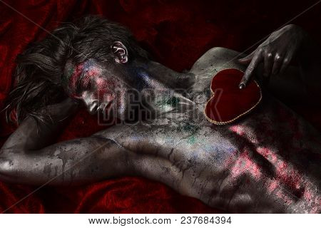 Man with nude torso holds red plush soft heart toy on chest, dark background. Depression and brake up concept. Guy on sad face with make up, covered with shimmering silver paint and colorful glitters. poster