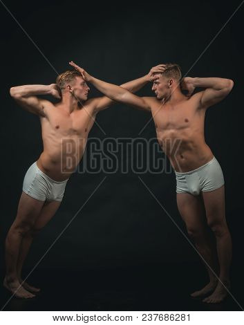 Twins Men With Muscular Body In Balance Pose. Circus Gymnasts At Pilates Or Yoga Training. Sport Wor