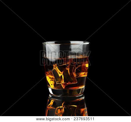 Glass Of Whiskey With Ice Isolated On Black Background