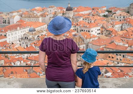 Caucasian Mother And Daughter Tourists Wearnig Blue Hats Standing On Top Of Old Town Walls In Dubrov