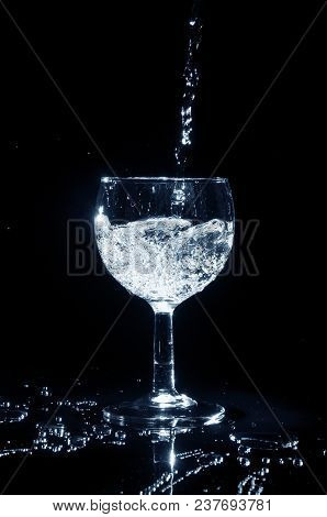 Pouring Water Into A Glass On Black Background.