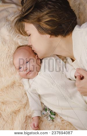 Mother And Newborn Daughter Lie On A Pink Plaid. They Are Dressed In Warm Knitted White Sweaters. Mo