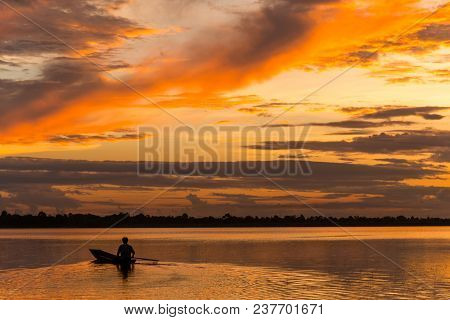 Sunset View In Rural With Silhouette Of A Man In Boat On The River In Rural Of Thailand