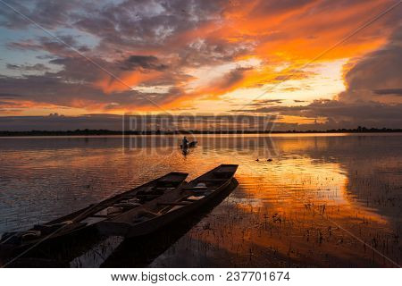 Sunset View In Rural With Silhouette Of A Man In Small Boat And  Two Small Boats Parking On The Rive