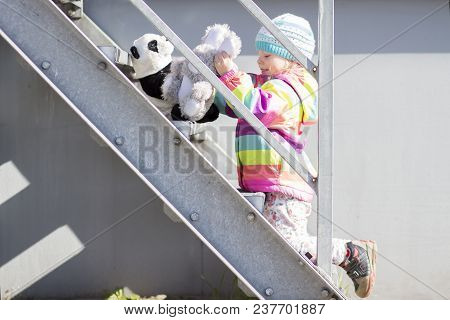 Little Girl Is Playing On Metal Staircase With Plush Toys. Baby Girl In Colored Jacket And Hat Plays