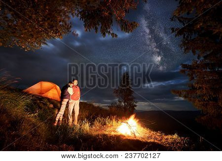 Romantic Evening Of A Young Couple Hikers In The Mountains By The Fire Under The Starry Sky In Night