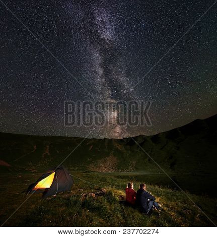 Rear View Young Two Persons Hikers Sitting Around The Campfire Near Tent, Admiring Mountains And Lak