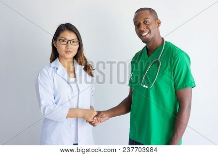 Happy Young Male Physician And Female Doctor Shaking Hands. Smiling African American Medic Wearing G