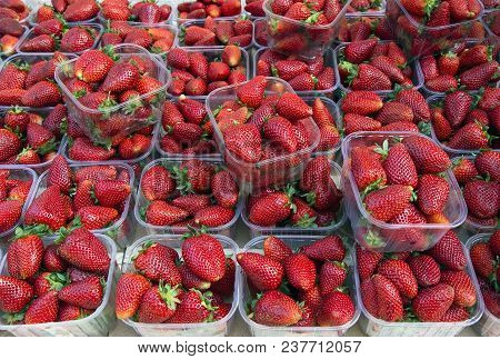 Fresh Strawberries In Baskets For Sale At Farmers Market. Food Background.