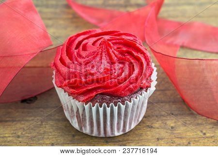 Red Velvet Cup Cake With Red Ribbon On Rustic Wooden Table