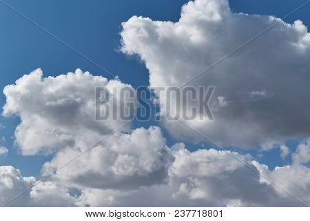 Some big Cumulus clouds on a clear blue sky. Clouds are illuminated by sunlight. Summer weather before the rain. Backdrop or background Wallpapers and images. poster